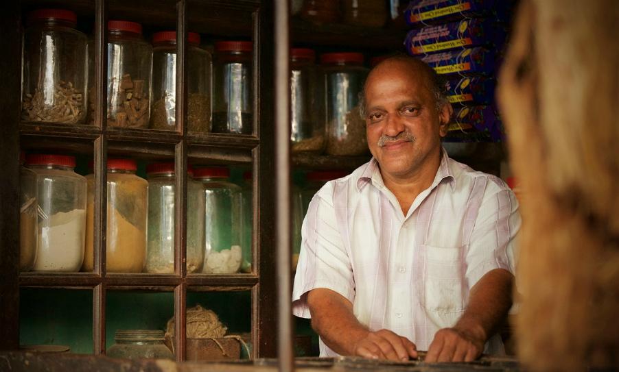 Fotografie Kaashinatha Shettyho, Narendranathův dědeček, kterého můžeme v obchůdku vidět společně s hinduistickými bohy.
